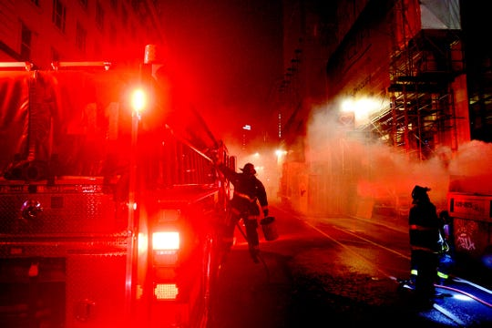 A firefighter prepares to extinguish a dumpster fire on Taylor St. in San Francisco on Saturday, May 30, 2020. Widespread vandalizing occurred at businesses throughout San Francisco following the death of George Floyd, a handcuffed black man in police custody in Minneapolis.