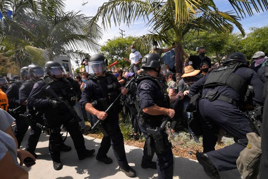 Los Angeles police officers move demonstrators back during a protest over the death of George Floyd, Saturday, May 30, 2020, in Los Angeles. Floyd died in police custody on Memorial Day in Minneapolis.