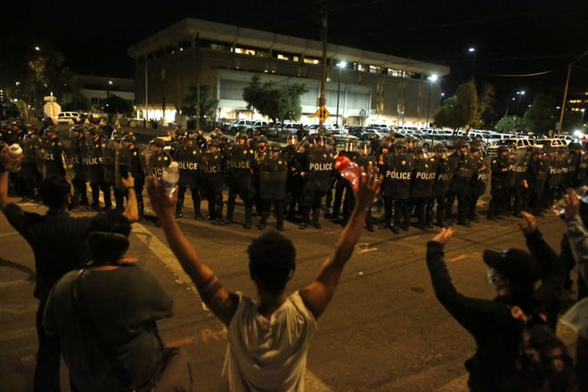 Protesters stand off with police outside Phoenix police headquarters during a protest in Phoenix on May 30, 2020.