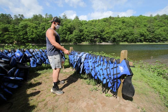 Alan Sipple is part of the canoe crew that shuttles guests from different landing sites along the Delaware River. He sprayed life jackets with disinfectant and they will sit for 72 hours between each use on Friday.