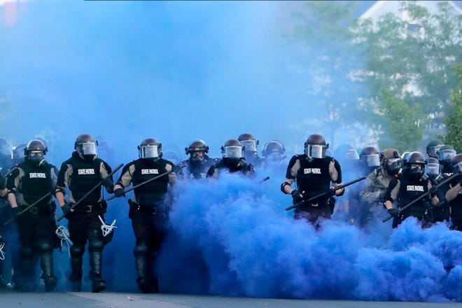 Minnesota State Police officers approach a crowd of protesters, Saturday, May 30, 2020, in Minneapolis. Protests continued following the death of George Floyd, who died after being restrained by Minneapolis police officers on Memorial Day. (AP Photo/Julio Cortez)
