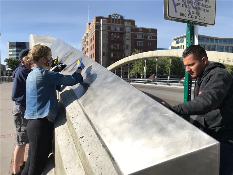 Edgar Gonzalez of Sparks cleans graffiti off the Virginia Street bridge May 31, 2020, the day after protests downtown turned violent and caused significant damage to the area.