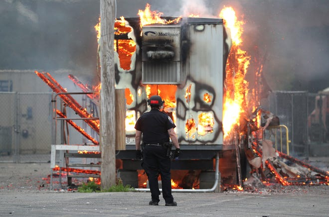 A police office stands in front of a burning trailer at May 30 protests in Rochester.