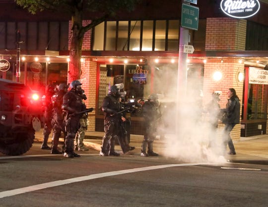 Police use tear gas and fire paintballs at a protester who refused to get out of the street as they advanced to clear crowds, in Salem, Oregon, early May 31, 2020.