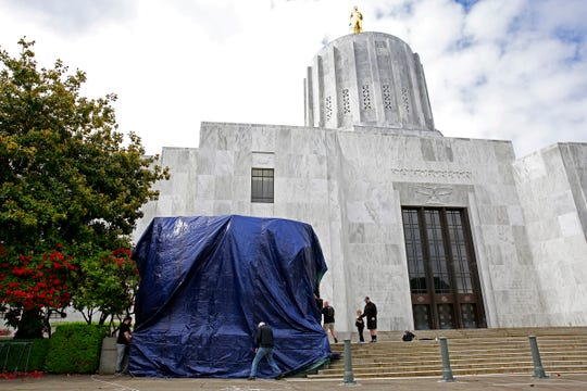 A tarp is secured over a spray-painted relief in front of the Oregon State Capitol Building in Salem, Oregon, on Sunday, May 31, 2020.