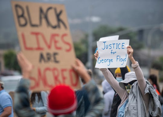 """A woman holds a """"Justice for George Floyd"""" sign during the  ÒCall for JusticeÓ demonstration in Monterey, Calif, on Saturday, May 30, 2020."""