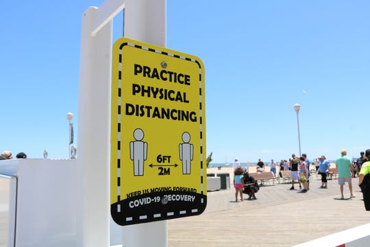 Signs posted by the town of Ocean City remind guests to practice physical distancing on May 31, 2020 in Ocean City.