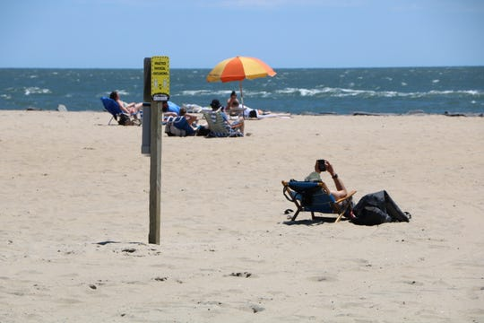 A woman checks her phone and lounges in a beach chair next to a sign that reminds beachgoers to practice physical distancing on May 31, 2020 in Ocean City.