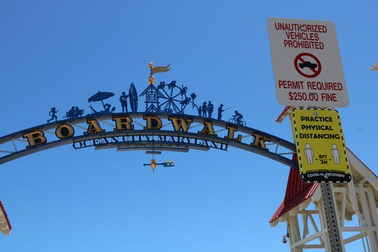 A sign posted in front of the Ocean City Boardwalk arch reminds visitors to practice social distancing while on the Boardwalk and beach on May 31, 2020 in Ocean City.