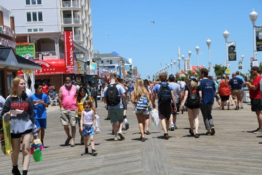 Visitors walk along the Ocean City Boardwalk on May 31, 2020. Most individuals weren't wearing masks despite calls from town officials to practice proper social distancing efforts to protect themselves and others.