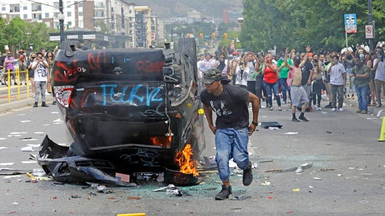 A protester runs from a burning police car after it was flipped over during a rally protesting the death of George Floyd Saturday, May 30, 2020, in Salt Lake City. Protests across the country have escalated over the death of George Floyd who died after being restrained by Minneapolis police officers on Memorial Day, May 25. (AP Photo/Rick Bowmer)