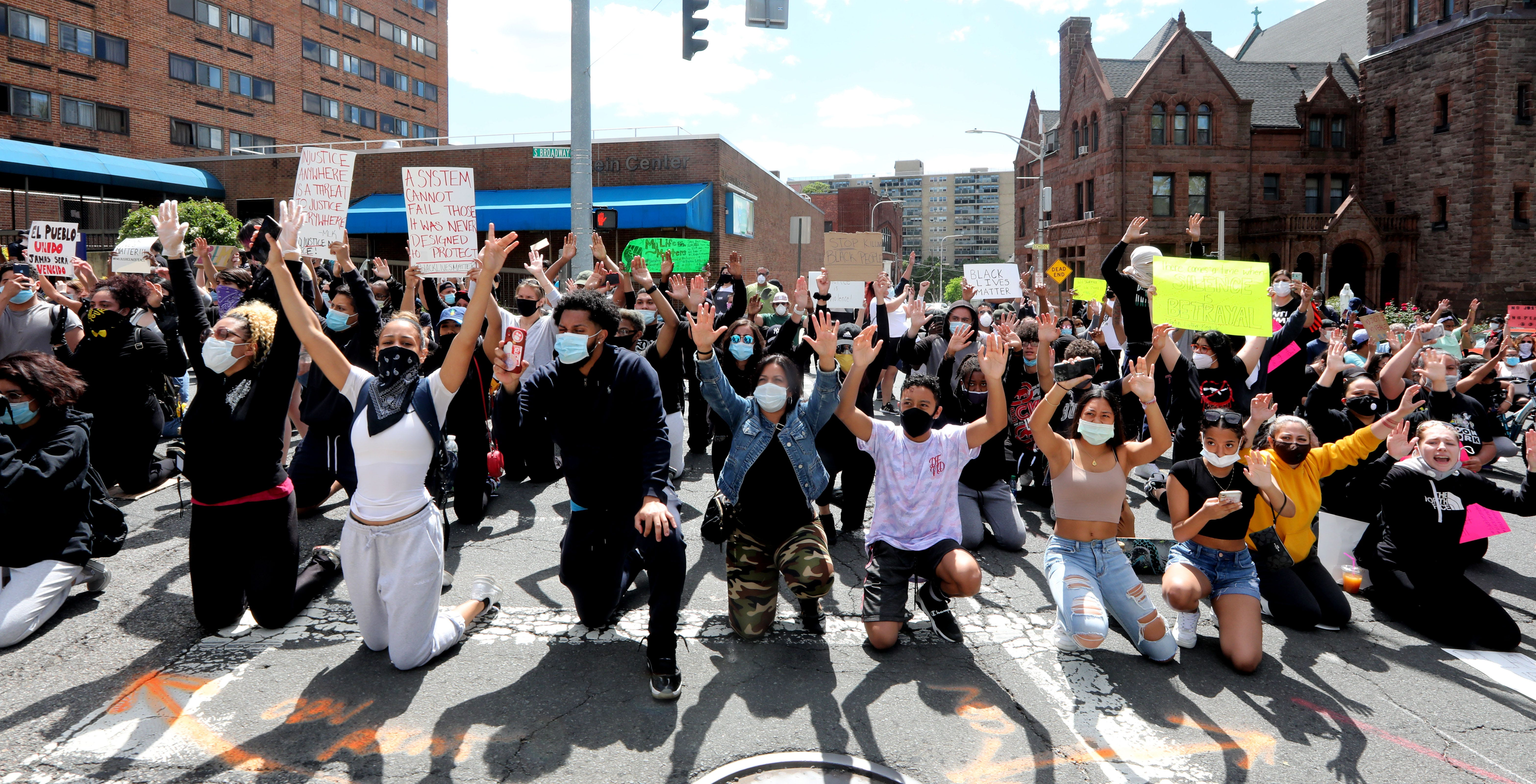 Protesters raise their hands as they kneel in front of the Yonkers police headquarters during a march and rally in Yonkers, N.Y. May 31, 2020 to protest the death of George Floyd in Minneapolis.