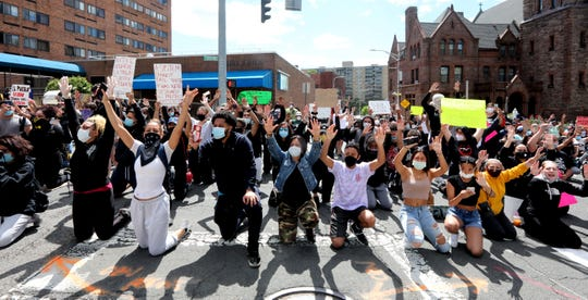 Protestors raise their hands as they kneel in front of the Yonkers police headquarters during a march and rally in Yonkers, N.Y. May 31, 2020 to protest the death of George Floyd in Minneapolis.