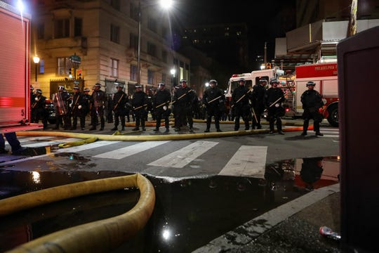A line of police gather in front of a fire near Walnut and 19th street on Saturday night in Philadelphia. The city instituted a curfew as crowds protested against police violence after the death of Minnesota man George Floyd.