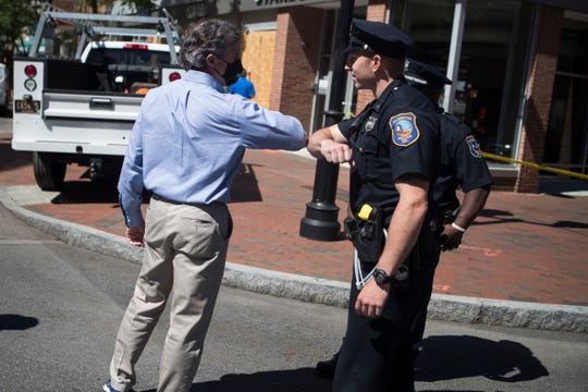 Governor John Carney elbows with a member of the Wilmington Police Department Sunday, May 31, 2020, on Market Street in Wilmington.