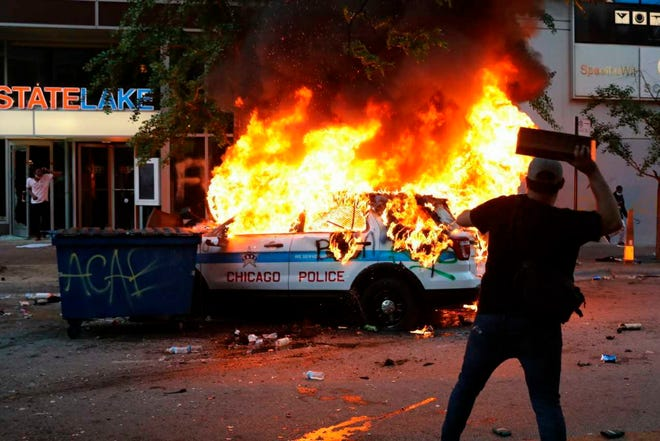 A Chicago police vehicle is set on fire during violent protests Saturday, May 30, 2020, as outrage builds over the killing of George Floyd, a black man who died in Minneapolis on May 25 after a police officer pressed his knee into his neck for several minutes.