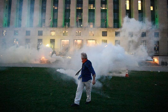 """Tear gas is sprayed outside the Metro Courthouse in Nashville, Tenn., Saturday, during the """"I Will Breathe"""" rally to protest the death of George Floyd, a black man who died after being pinned down by a white Minneapolis police officer on Memorial Day."""