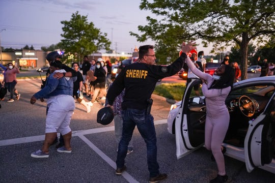 Genesee County Sheriff Chris Swanson high-fives a woman who called his name as he marched with protesters in memory of George Floyd on May 30 in Flint Township, Mich.