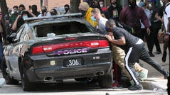 Protesters try to overturn a damaged Cleveland police cruiser during a protest seeking justice in the death of George Floyd, Saturday, May 30, 2020 in Cleveland.