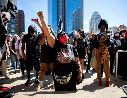 "Rhonda Mathies, 69, of Louisville, gets down on her knees as she sings ""We Shall Overcome"" along with the crowd Sunday, May 31, 2020, during a Black Lives Matter healing rally in front of KFC Yum! Center in downtown Louisville."