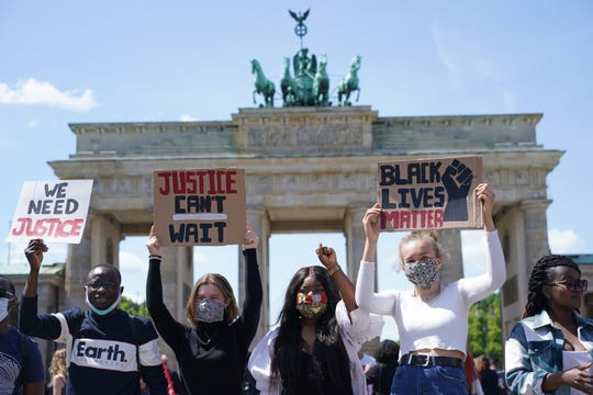 People attend a rally against racism in front of the Brandenburg Gate on May 31 in Berlin after the death of George Floyd in the USA.