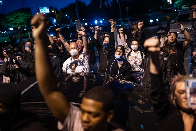 People raise their fists after marching in Flint Township, Michigan, on May 30. Protesters marched to the police department headquarters, where they were met by officers in riot gear before the Genesee County Sheriff agreed to march with them.