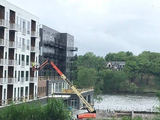Workers put finishing touches on the Willow apartment/commercial building in Appleton's RiverHeath complex.
