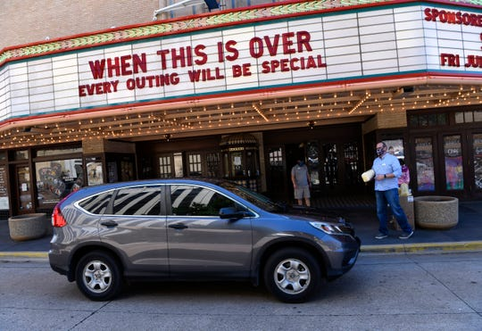 A car pulls up under the marquee of the Paramount Theatre Friday as Executive Director George Levesque waits to hand the driver a bag of popcorn.