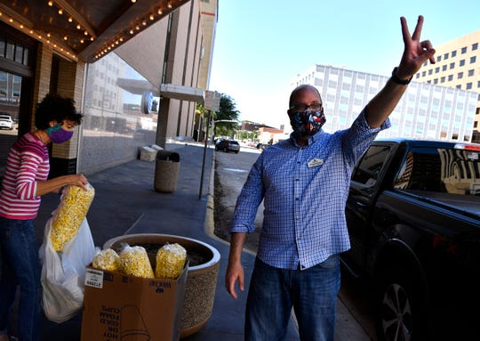 Paramount Theatre Executive Director George Levesque gets the signal for two bags of popcorn Friday. The theater is selling bags of popcorn for $10 each starting at 4 p.m. Fridays.