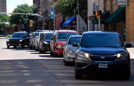 Cars line up along Cypress Street Friday to buy popcorn from the Paramount Theatre.