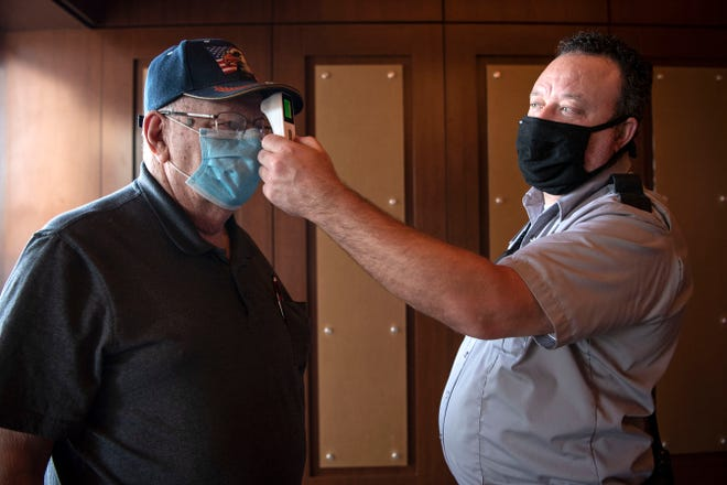 Gerald Paddock has his temperature taken before entering FireKeepers Casino Hotel on Monday, June 1, 2020 in Battle Creek, Mich. FireKeepers reopened to the public with new social distancing practices in place.