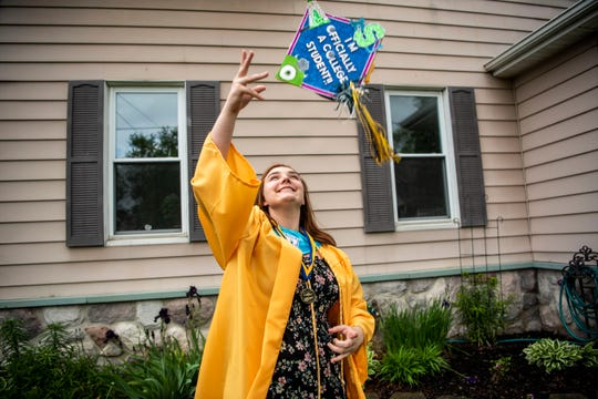 Battle Creek Central senior Maddi Mahar poses for a portrait in her graduation cap and gown on Thursday, May 28, 2020 at her home in Battle Creek, Mich. Mahar is following in her late mother's footsteps and attending Michigan State University in the fall, where she will study zoology.
