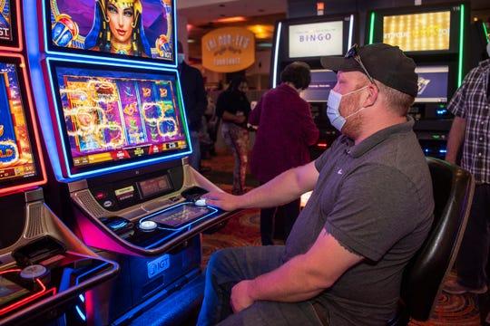 Perry Barnett dari Fremont, Indiana menggunakan mesin slot pada hari Senin, 1 Juni 2020 di FireKeepers Casino Hotel di Battle Creek, Mich. FireKeepers dibuka kembali ke publik dengan praktik sosial jarak baru di tempat.