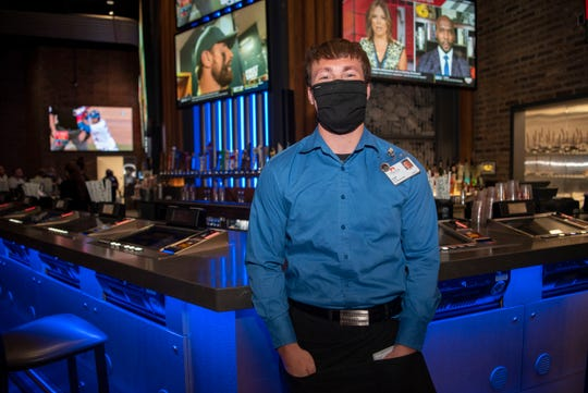 """Server Austin McKenzie poses for a portrait on Monday, June 1, 2020 at FireKeepers Casino Hotel in Battle Creek, Mich. """"It's good to get back to work, great to be back interacting with my customers and the people I work with,"""" said Austin McKenzie."""