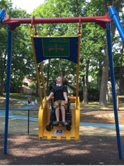 Connor Ford and his family have enjoyed using the Liberty Swing at OurSpace inside Recreation Park in Binghamton.