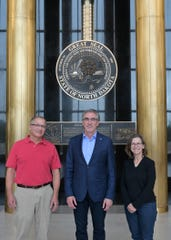North Dakota Gov. Doug Burgum, center, with Marc and Cindy Miller in the Memorial Hall of the Capitol Building in Bismark, ND, last fall.