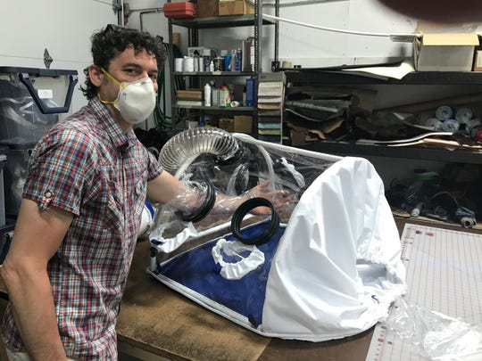 Matt Renna of Queen City Dry Goods demonstrates how to use the negative pressure tent he helped build with a UVM Medical Center anesthesiologist.