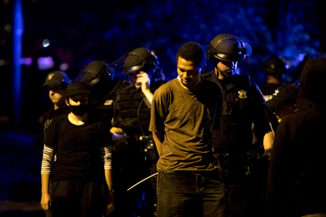 A protester is taken into custody is arrested for violating curfew on Green Street in OTR on Sunday, May 31, 2020. This marked the third day of protests over the death of George Floyd in Minneapolis at the hands of police.