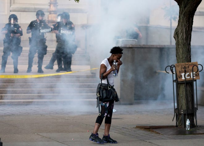 A protester reacts to tear gas in front of the Hamilton County Courthouse in Cincinnati, on Sunday, May 31, 2020. This marked the third day of protests over the death of George Floyd in Minneapolis at the hands of police.