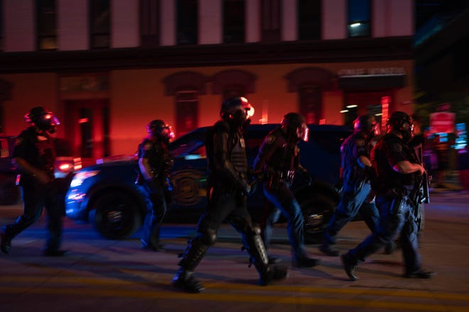 Police in riot gear walk away after deploying tear gas on Fulton Avenue in downtown Grand Rapids, Mich., Saturday, May 30, 2020, during protests over the death of George Floyd.