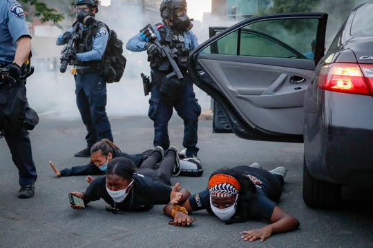 Motorists are ordered to the ground from their vehicle by police during a protest on South Washington Street, Sunday, May 31, 2020, in Minneapolis.