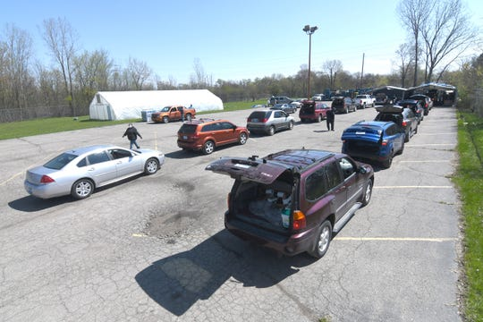 Dozens of cars arrive with their trunks and hatchbacks open as volunteers prepare to load cases of bottled water, milk and produce at the Greater Holy Temple parking lot in Flint on Thursday, May 7, 2020.