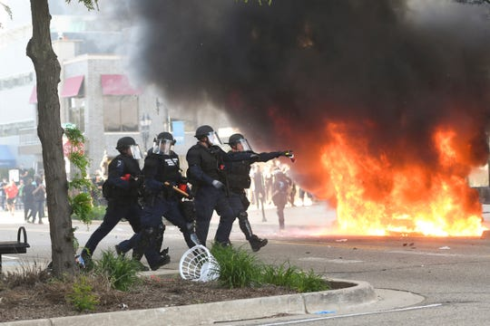 Police move to block off an intersection in downtown Lansing near S. Washington Avenue and E. Michigan Avenue Sunday, May 31, 2020, as a car burns in the background.