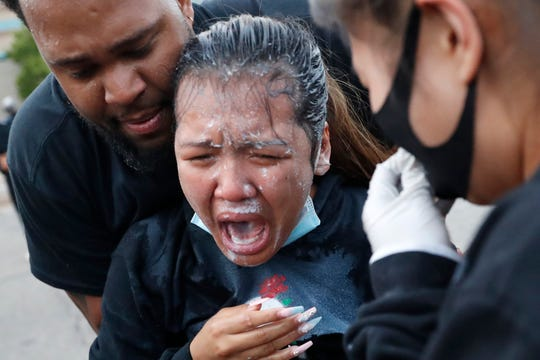 A woman is helped after being hit with pepper spray after curfew on Sunday, May 31, 2020 in Minneapolis.