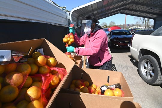 Kay Lewis, water coordinator, grabs bags of oranges for clients at Greater Holy Temple in Flint on Thursday, May 7, 2020.