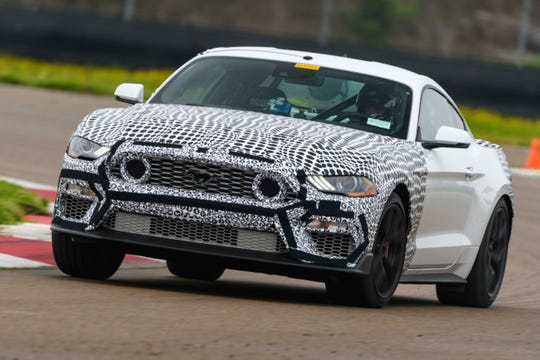 The 2021 Ford Mustang Mach 1, shown testing in camouflage, has signature air intakes in the grille.
