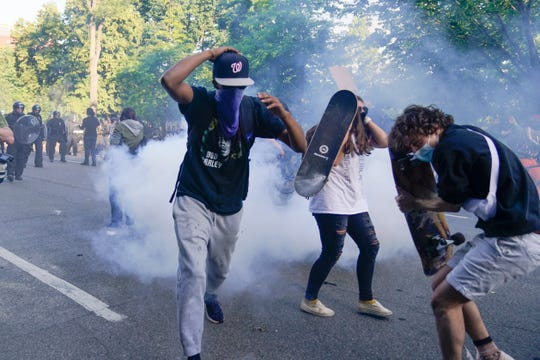 Demonstrators, who had gathered to protest the death of George Floyd, begin to run from tear gas used by police to clear the street near the White House in Washington, Monday, June 1, 2020. Floyd died after being restrained by Minneapolis police officers.