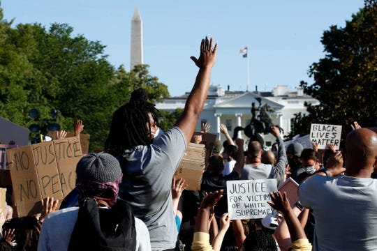 Demonstrators gather in Lafayette Park to protest the death of George Floyd, Monday, June 1, 2020, near the White House in Washington. Floyd died after being restrained by Minneapolis police officers.