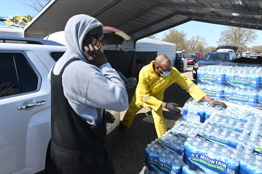 Floyd Macklin, left, and Cory Anderson grab cases of bottled water for clients at Greater Holy Temple in Flint on Thursday