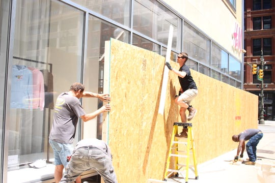 A crew from OnSite Solutions boarded-up the windows of the H&M store on Woodward Monday afternoon